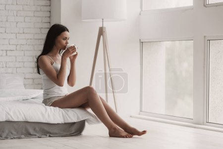 Young Woman Drinking Coffee on Bed at Home. Beautiful Young and Beautiful Woman Relaxing in Bed. Morning Concept. Wake Up. A Girl Waking Up in The Morning.