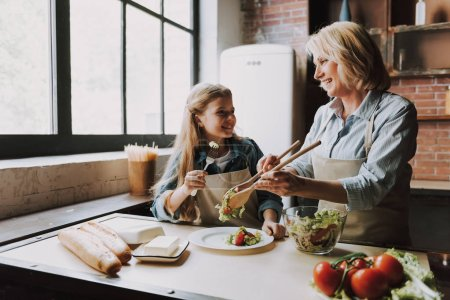 Photo for Cute Grandma and Granddaughter Cooking Salad. Grandma and Granddaughter Cooking Food. Vegetable Salad. Diet. Dieting Concept. Healthy Lifestyle. Cooking At Home. Prepare Food - Royalty Free Image