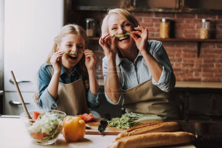 Photo for Grandma and Granddaughter Having Fun in Kitchen. Grandma and Granddaughter Cooking Food. Vegetable Salad. Diet. Dieting Concept. Healthy Lifestyle. Cooking At Home. Prepare Food - Royalty Free Image