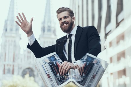Photo for Smiling Handsome Businessman Meeting Somebody. Guy Handing Up. Man Waiting Somebody. Bearded Serious Man Wearing Suit and Glasses, Standing Outdoor and Reading Newspaper. Business Concept. - Royalty Free Image