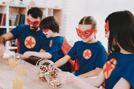 Young Family In Superhero Suits. Dinner Concept. Masks And Raincoats. Bright Room. Resting Together. Juice And Cereals. Get Ready. Healthy Lifestyle. Kids With A Parents. Active Leisure.