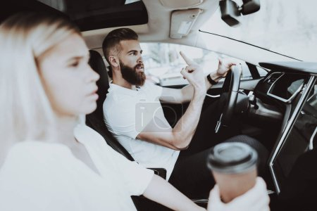 Man Behind The Wheel Of Tesla Car. Girl At Front Seat. Innovation Technology. New Generation Electro Hybrid Vehicle. Luxury Design. Futuristic Power. Hands On Display. Test Driving. Road Talking.
