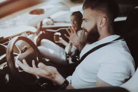 Man Behind The Wheel Of Tesla Car. Girl At Front Seat. Innovation Technology. New Generation Electro Hybrid Vehicle. Luxury Design. Futuristic Power. Fasten Seatbells. Test Driving. Road Talking.