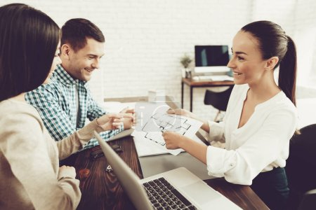 Young Man and Woman with Smiling Realtor in Office. Blueprint on Wooden Desk. Real Estate Concepts. Young Couple. Buying New Home. Family in Office. Rental Agent Concept. Happy Family.