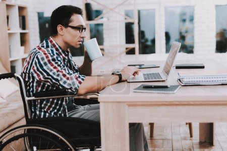 Young Disabled Man on Wheelchair Working at Home. Man on Wheelchair. Disabled Guy. Checkered Shirt. Wooden Table. Wooden Shelf. Freelancer at Home. Worker on Wheelchair. Work for Disabled Man.