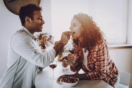 Photo pour Petit ami nourrit sa petite amie avec des fraises. Week-end Concept. Refroidissement à la cuisine. Vacances au repos. Souriant ensemble. Je m'amuse. Un rendez-vous romantique. Couple afro-américain buvant du vin . - image libre de droit