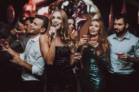 Woman in Black. Dress. Trendy Nightclub. Have Fun. Background. Cheerful. Smile. Smiling Girl.Singing Songs. Handsome Men. Beautiful Girls. Friends at Karaoke Club. Karaoke Club. Celebration.
