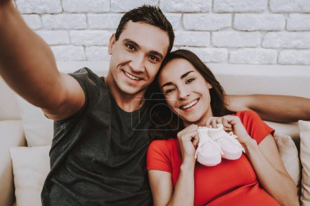 Photo for Selfie. Husband and Pregnant Wife. Parenthood. Sit. Together on Couch. Love Each Other. Home. Sweet. Sofa. Happy Together. Motherhood. Relaxation. Tenderness. Resting. Happiness. Birth. Domestic Life. - Royalty Free Image