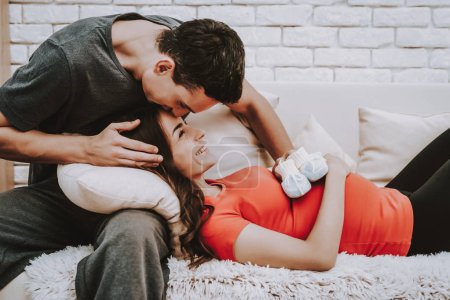 Together on Couch. Love Each Other. Home. Sweet. Sofa. Husband and Pregnant Wife. Sit. Happy Together. Motherhood. Relaxation. Tenderness. Resting. Happiness. Birth. Parenthood. Domestic Life.