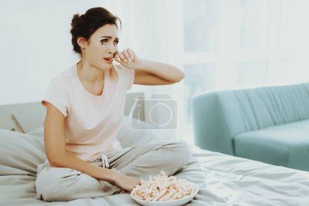 Photo pour La femme qui pleure solitaire mange Français Fries sur le lit. Vacances malheureux. Triste fin de semaine. Larmes sur le visage. Journée ensoleillée. Seul dans la chambre à coucher. Fille déçue. Maquillage gâté. Mascara a coulé. - image libre de droit