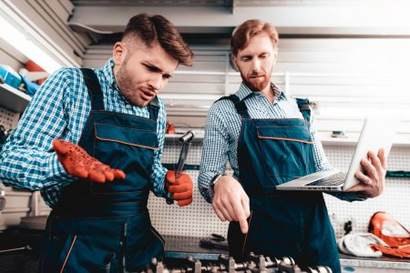Two Auto Mechanics Work Together In Garage. Wrench Using. Laptop Screen Staring. Information Sharing. Professional Uniform. Confident Engineering Specialist Team. Service Station Concept.