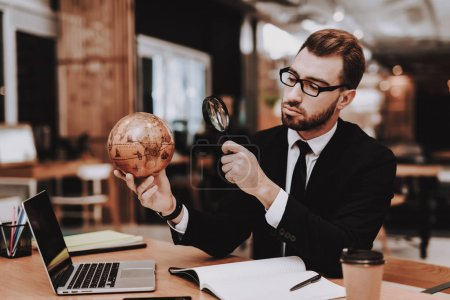 Photo for Magnifying Glass. Office. Business Suit. Globe. Project. Laptop. Sit. Brainstorm. Young Guy. Businessman. Work. Creative Worker. Ideas. Businesspeople. Workplace. Inspiration. Comfortable Office. - Royalty Free Image