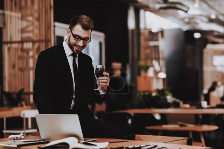 Photo for Brainstorm. Glass of Wine. Business Suit. Laptop. Sit. Young Guy. Businessman. Working in Office. Creative Worker. Creates Ideas. Businesspeople. Workplace. Inspiration. Comfortable Office. - Royalty Free Image