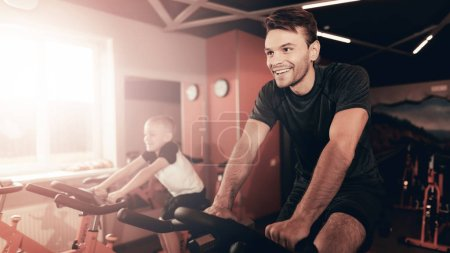 Father And Son Are Training On Bike Trail In The Gym. Parenthood Relationship. Sporty Family Concept. Active Lifestyle. Happy Childhood. Holiday Leisure. Working Out Together. Fitness Day.