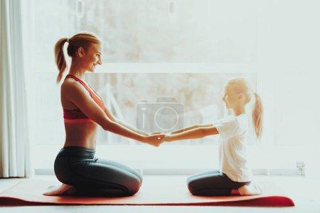 Photo pour Mère et fille assises sur le tapis de gymnase. Concept de yoga. Pose de méditation. Mode de vie actif. Tenez-vous la main. Fitness à la maison. Loisirs de vacances. Équilibre corporel. Exercice sportif. Matin ensoleillé . - image libre de droit