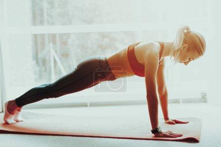 Jeune femme sportive fait Push Ups sur le tapis de Gym. Mode de vie actif. Fait de Fitness à la maison. Loisirs de vacances. Balance du corps. Exercice de sport. Triceps exercices de formation. Journée ensoleillée