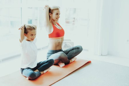 Mum And Daughter Yoga Training. Lotus Position. Active Lifestyle. Relaxing Together. Fitness At Home. Holiday Leisure. Body Balance. Sport Exercise. Sunny Day. Arms Behind The Back.