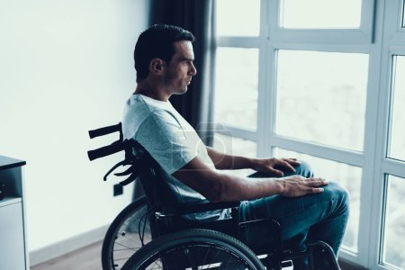 Disabled Person Sits in Wheelchair Against Window. Closeup Profile of Sad Caucasian Man Wearing White T-Shirt and Jeans and Look at Large Panoramic Window in Bright Living Room or Hospital.