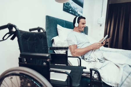 Invalid Uses Pad and Listens to Music in Bed. Handsome Smiling Caucasian Disabled Person Relaxing in Bed With White Linens near Wheelchair in Bright Bedroom. Man in Headphones Holds Tablet.