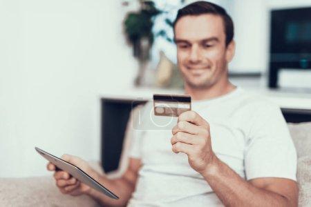 Foto de Persona borrosa tiene tarjeta de crédito y utiliza Tablet. Atractivo hombre sonriente sentada en el sofá hace compras en línea y que muestra satisfecha expresión de la cara en la moderna sala de estar en casa - Imagen libre de derechos