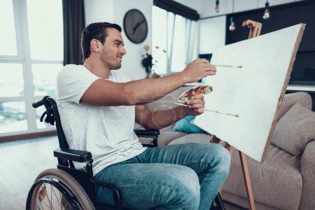 Beau jeune homme handicapé Image. Portrait d'une personne caucasienne souriante en fauteuil roulant en face du chevalet portant des vêtements décontractés tenant des pinceaux pendant qu'elle était assise dans le salon à la maison