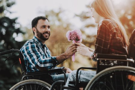 Couple of Disabled People on Wheelchairs on Date in Park. Young Man with Flowers. Woman on Wheelchair. Date in Summer Park. Romantic Relationship. Recovery and Healthcare Concepts. Happy Couple.