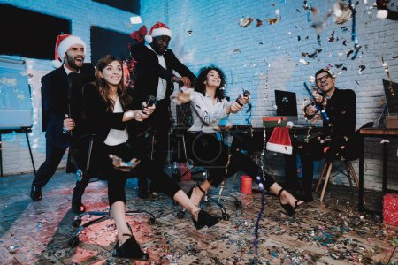 Photo for Smiling Businesspeople on New Year Party in Office. New Year Eve. Smiling Businessman. Man in Santa Claus Cap. Celebrating of New Year. Modern Office. People Have Fun. Indoor Party. Confetti on Floor. - Royalty Free Image