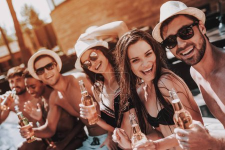 Young Friends with Alcoholic Drinks at Poolside. Group of Young Smiling People holding Bottles of Beer and having Fun at Poolside. Happy Friends Enoying Pool Party. Summer Vacation Concept