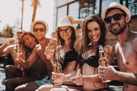Photo for Young Friends with Alcoholic Drinks at Poolside. Group of Young Smiling People holding Bottles of Beer and having Fun at Poolside. Happy Friends Enoying Pool Party. Summer Vacation Concept - Royalty Free Image
