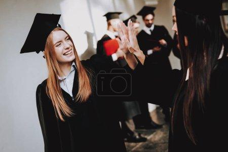 Cheerful. Celebration. Cap. Architecture.Happiness. Asian Girl. Intelligence. Diploma. Standing. Corridor. University. Robes. Graduate. Happy. Good Mood. University. Campus. Knowledge. Mortar Board.