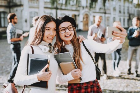 Photo for Selfi. Girls. Happy Together. Students. Courtyard. Books. Standing in University. Good Mood. University. Knowledge. Architecture. Happiness. Intelligence. Celebration. Campus. Man. Friends. Happy. - Royalty Free Image