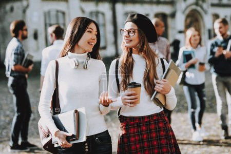 Photo for Happiness. Coffee. Girls. Happy Together. Students. Courtyard. Books. Standing in University. Good Mood. University. Knowledge. Architecture. Intelligence. Celebration. Campus. Man. Friends. Happy. - Royalty Free Image