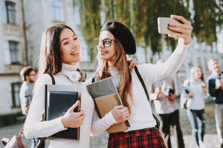 Photo for Happy Together. Selfi. Girls. Students. Courtyard. Books. Standing in University. Good Mood. University. Knowledge. Architecture. Happiness. Intelligence. Celebration. Campus. Man. Friends. Happy. - Royalty Free Image