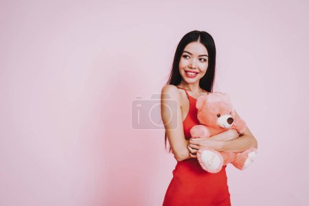 Girl in Red Dress. Pink Background. Celebrating Women's Day. March 8. Girl with Bear. Smiling Girl. Happy Woman. Happy Emotions. International Party. Beautiful Woman. Taddy Bear. Woman with Taddy Bear