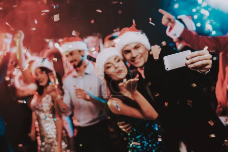 Photo for Happy People Taking Selfie on New Year Party. Happy New Year Concept. People Have Fun. Indoor Party. Celebrating of New Year. Young Woman in Dress. Young Man in Red Cap. Using Smartphone. - Royalty Free Image