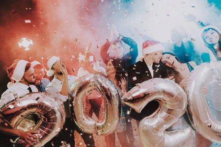 Photo pour Personnes souriantes avec ballons célébrant le nouvel an. Fête du nouvel an. Jeune femme en robe. Jeune homme en costume. Cap de Santa Claus. Gens avec des ballons gris. Bonne année. Les gens sont amuser. - image libre de droit