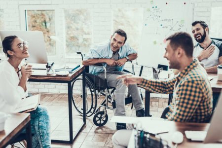 Photo for Young Workers Have Discussion in Modern Office. Brainstorm at Work. Smiling Woman. Man on Wheelchair. Smiling Manager. Teamwork in Office. Plan Presentation. Communication with Colleagues. - Royalty Free Image