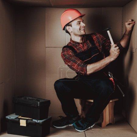 Worker in Orange Helmet Sitting in Cardboard Box. Young Man in Uniform. Uncomfortable Life. Personal Spase Concept. Uncomfortable House Concept. Young Introvert. Worker with Tools.