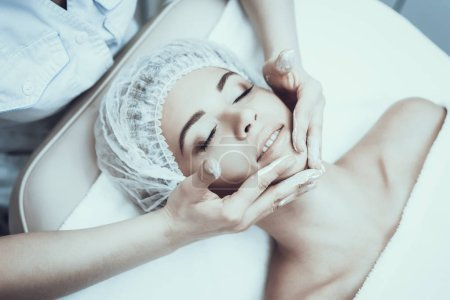 Photo for Young Woman in Spa Salon for Cleansing Massage. Girl in Beauty Salon. Modern Cosmetology. Proffesional Cosmetologist. Doctor in White Coat. Women's Beauty Concept. Skin Care and Cleaning. - Royalty Free Image