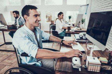 Photo pour Homme en fauteuil roulant travaillant sur ordinateur au bureau. Jeune homme handicapé. Homme en fauteuil roulant. Recovery and Healthcare Concepts. Travail d'équipe au bureau. Jeune ouvrier. L'homme assis. Homme avec ordinateur . - image libre de droit