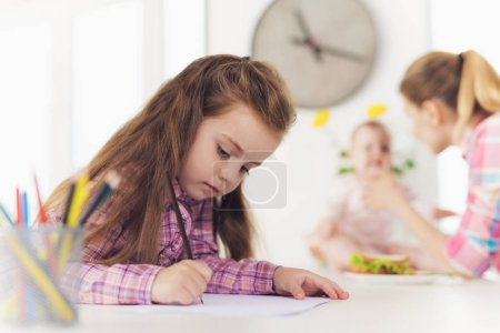 Girl Painting While Mother Feeding Younger Sister. Cute Pretty Child Drawing with Colored Pencils at White Table. Young Mom with Baby Blurred Behind. Children Activity Concept