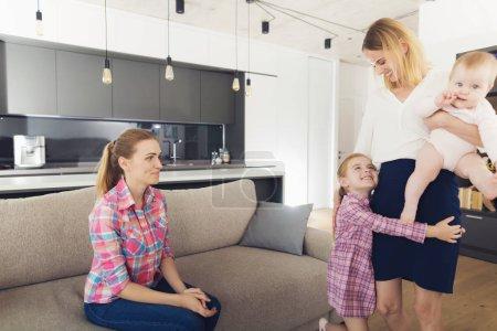 Photo pour Babbysitter regardant Kids étreindre mère. Heureux, femme d'affaires bébé sur ses mains et fille embrassant les pieds mères en salon lumineux. Nounou souriante, assis sur le canapé confortable - image libre de droit