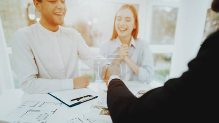 Young Couple. Meeting With Rieltor Concept. Bright Office. Making A Contract. Buying A Property. Panoramic Windows. Business Meeting. Customer And Buyer. Offer Discussion. Professional Agreement.