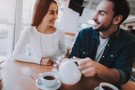 Happy Together. Leisure Time. Teapot. Together in Cafe. Cheerful Girl. Drink Tea. Have Fun. Tea Party. Smiling People. Enjoyment. Guy and Girl. Bonding. Good Relationship. Happy Holidays. Love.
