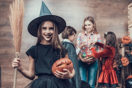 Young Girl wearing Witch Costume Holding Broom. Woman gives Candys to Kids wearing Halloween Costumes. Happy Halloween Party with Children Trick or Treating. Celebration of Halloween