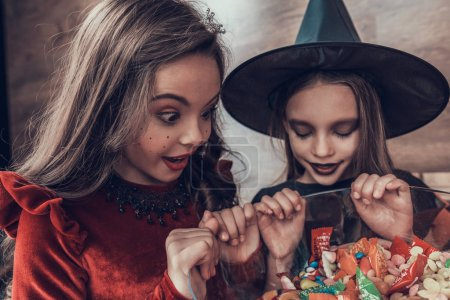 Kids in Costumes looking into Bowl full of Candys. Happy Halloween Party with Children Trick or Treating. Young Adorable Girls having Fun and getting Sweets. Celebration of Halloween