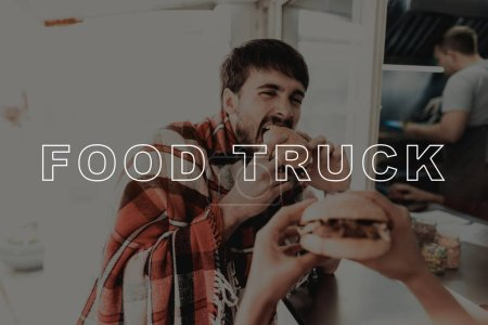 Photo for Young Couple Wrapped In Plaids. Food Truck. Coffee To Go. Having Dinner Together. Young And Beautiful. Stylish Teenagers. Cold Day. Big City Life. . Love Each Other. Burger Eating. - Royalty Free Image