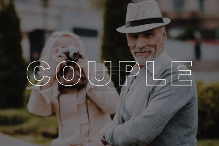 Photo for Alley in Park. Take Pictures. Vintage Film Camera. Happy Together. Bubbly Relationships. Love Story. Relationships. Two Pensioners. Old Couple. Retired. Leisure Time. Have Fun. Sit. Smiling. Summer. - Royalty Free Image
