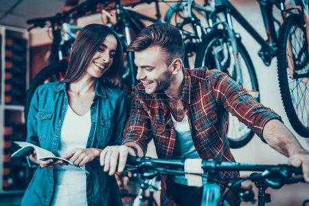 Photo pour Joyeux jeune couple parlant tout en choisissant un nouveau vélo. Belle fille en denim vêtements cycle d'achat parler avec beau consultant portant à carreaux chemise et rires dans le magasin de sport - image libre de droit