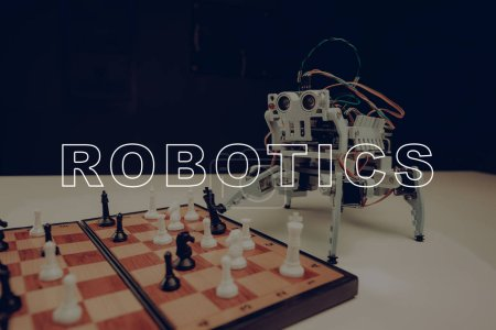 Close Up. A Small Gray Robot Is Playing Chess. Empty Room. Workshop Background. Innovation Technology. Artifical Intelligence. Technical Industry. Four Limbs. Remote Control. Cyborg Education.